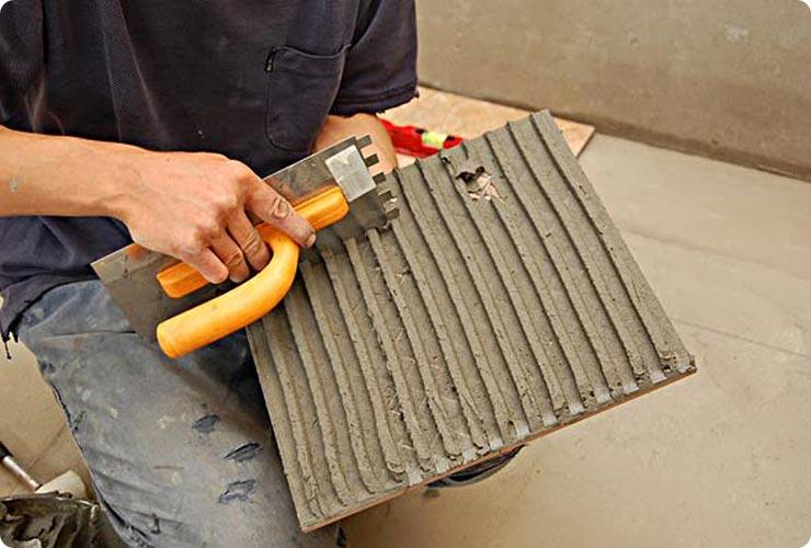 Наносит клей на плитку