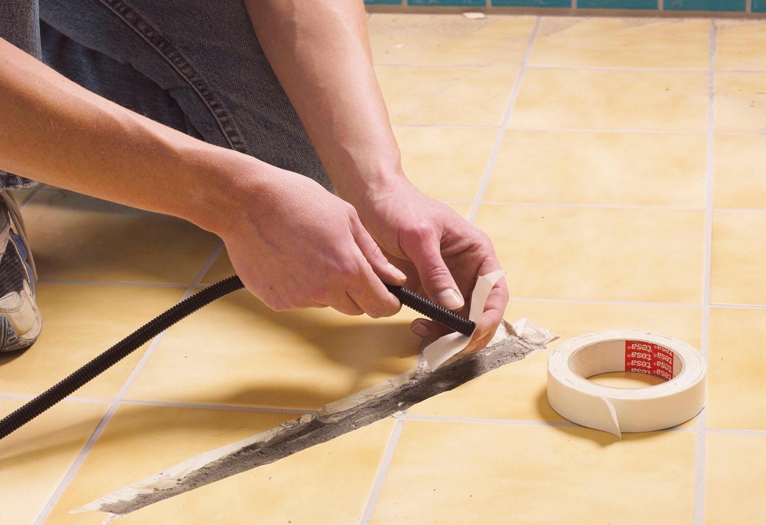 Укладка кабеля перед монтажом электрического теплого пола под плитку