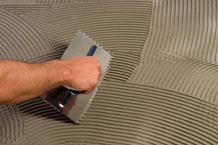 Наносит плиточный клей