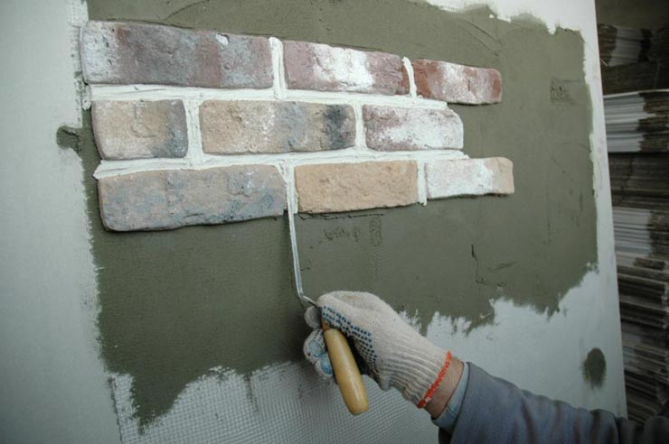 Клеит гипсовую плитку на стену