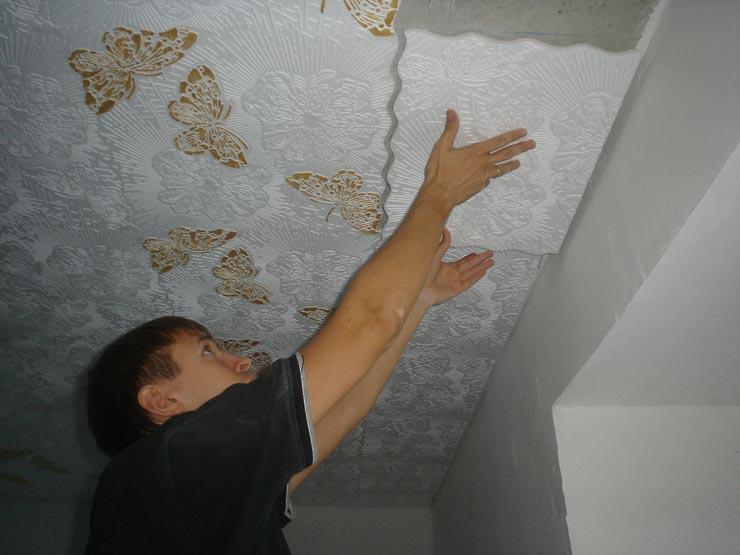 Клеит плитку на потолок в зал