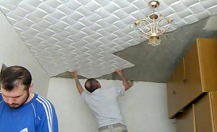 Клеит потолочную плитку ромбом
