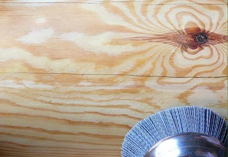 зачищает лак на деревянной стене